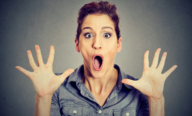 excited surprised woman screaming isolated on gray wall background